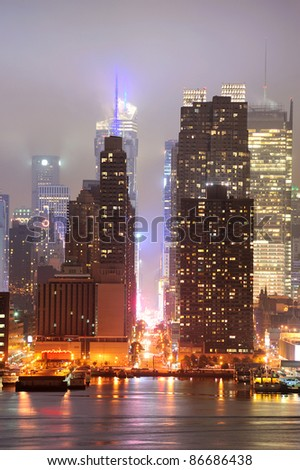 New York City Manhattan midtown 42nd street skyline at foggy night with skyscrapers over Hudson River viewed from New Jersey. - stock photo