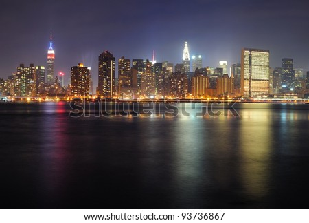 New York City Manhattan midtown panorama at night with skyscrapers illuminated over east river