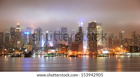 New York City Manhattan midtown panorama skyline at night with skyscrapers over Hudson River viewed from New Jersey.