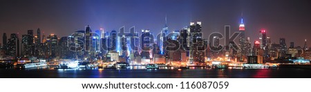 New York City Manhattan midtown skyline at night with skyscrapers lit over Hudson River with reflections. - stock photo
