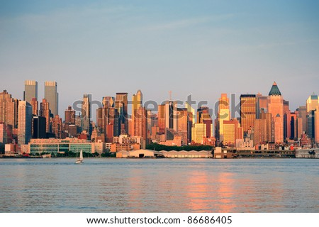 New York City Manhattan midtown skyline at sunset with reflection over skyscraper and river. - stock photo
