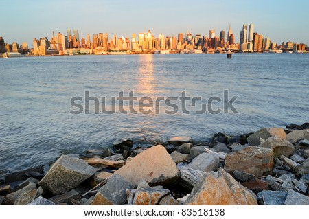 New York City Manhattan midtown skyline at sunset with reflection over skyscraper and river viewed from New Jersey Hudson River Shore with rocks. - stock photo