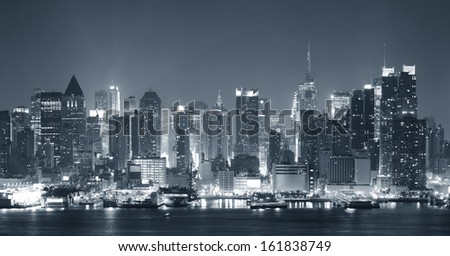 New York City Manhattan midtown skyline black and white at night with skyscrapers lit over Hudson River with reflections.  - stock photo