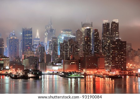New York City Manhattan midtown Times Square skyline at night with skyscrapers over Hudson River viewed from New Jersey. - stock photo