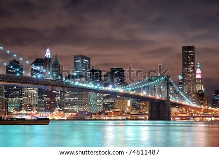 New York City Manhattan panorama view with Brooklyn Bridge at night with office building skyscrapers skyline illuminated over Hudson Rive - stock photo