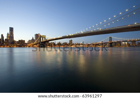 New York City Manhattan skyline and Brooklyn Bridge at dusk over Hudson River with skyscrapers - stock photo