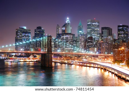 New York City Manhattan skyline and Brooklyn Bridge with skyscrapers over Hudson River illuminated with lights and busy traffic at dusk after sunset. - stock photo