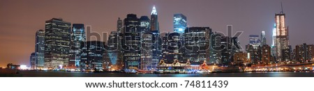 New York City Manhattan skyline panorama at night with Hudson river.