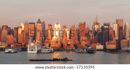 New York City Manhattan skyline panorama at sunset with skyscrapers and sunshine reflection over Hudson river. - stock photo