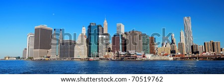 New York City Manhattan skyline panorama in the morning with skyscrapers over Hudson River with blue sky. - stock photo