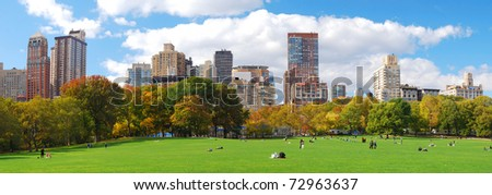 New York City Manhattan skyline panorama viewed from Central Park with cloud and blue sky and people in lawn. - stock photo