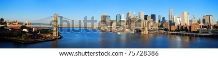 New York City Manhattan skyline panorama with Brooklyn Bridge and skyscrapers over Hudson River in the morning after sunrise. - stock photo