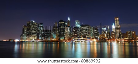 New York City Manhattan skyline panorama with office skyscrapers building illuminated with lights at night