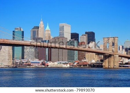 New York City Manhattan skyline with Brooklyn Bridge and skyscrapers over Hudson River in the morning after sunrise. - stock photo