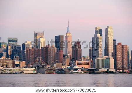 New York City Manhattan sunset panorama with historical skyscrapers over Hudson River with beautiful red color sunshine reflection viewed from New Jersey Weehawken waterfront. - stock photo