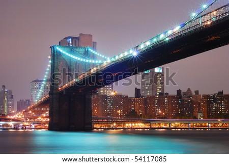 New York City Manhattan with Brooklyn bridge at night. - stock photo