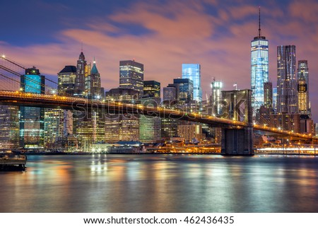 New York City - Manhattan with skyscrapers  and famous Brooklyn Bridge, great illumination and colorful clouds