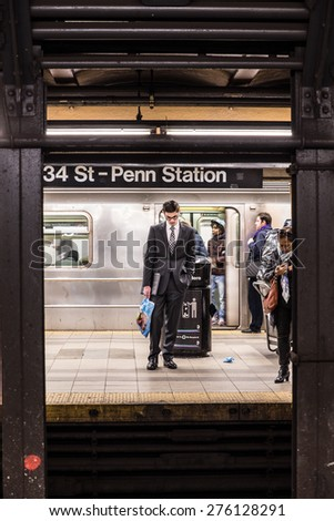 NEW YORK CITY - MARCH 13, 2015:  Scene from historic Penn Station in Manhattan with commuters on subway platform waiting for train. - stock photo