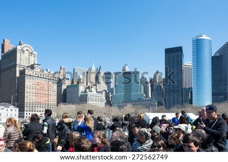 NEW YORK CITY - MARCH 9th 2015: Group of tourists in the ferry heading to Ellis Island taking photo of Manhattan City, USA - stock photo