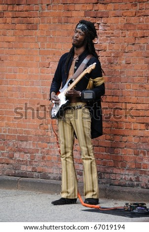 NEW YORK CITY - MAY 22: A busker performs Jimi Hendrix songs and dressed as Hendrix May 22, 2010 in New York, New York. - stock photo