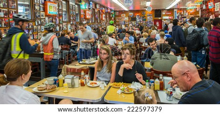 NEW YORK CITY - MAY 25, 2013: Katz's Delicatessen full of tourists and locals in Manhattan. Since its founding in 1888, it has become popular among locals and tourists alike for its pastrami sandwiches - stock photo