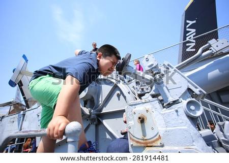 NEW YORK CITY - 25 MAY 2015: Mayor Bill de Blasio & Gen John Kelly presided over Memorial Day observances on Pier 86 by the USS Intrepid. Boy sights along 5 inch anti aircraft gun USS Intrepid - stock photo