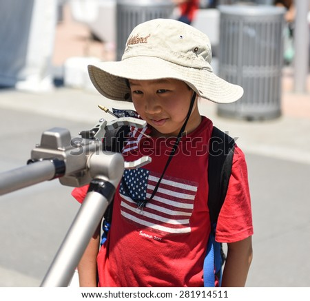 NEW YORK CITY - 25 MAY 2015: Mayor Bill de Blasio & Gen John Kelly presided over Memorial Day observances on Pier 86 by the USS Intrepid. Boy confronts Navy robotic arm - stock photo