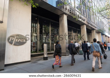NEW YORK CITY - MAY 2015: People crossing in front of Pfizer building. Pfizer is an American multinational pharmaceutical corporation, one of the world's largest pharmaceutical companies. - stock photo