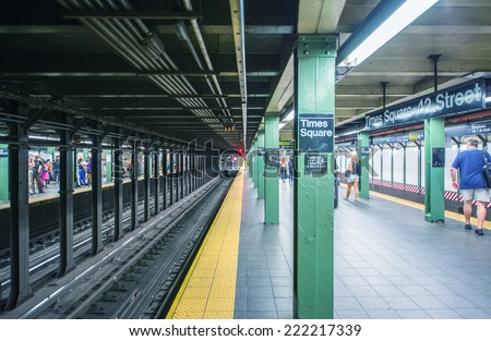 NEW YORK CITY - MAY 26: People walk in Times Square subway station, on May 26, 2013. Times Square subway station is located on 42nd Street and Eighth Avenue in Midtown Manhattan - stock photo