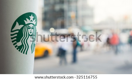 NEW YORK CITY - MAY 11, 2015: Starbucks Hot beverage coffee on table at Astor Place Store with blurred people in background walking. Starbucks is the largest coffeehouse company in the world. - stock photo