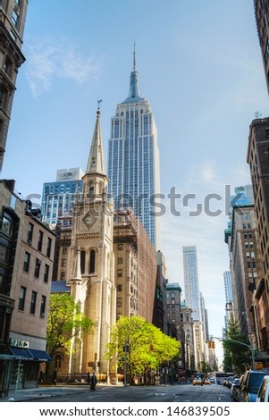 NEW YORK CITY - MAY 12: The Marble Collegiate Church and Empire State building on May 12, 2013 in New York. This church, founded in 1628, is one of the oldest continuous Protestant congregations. - stock photo