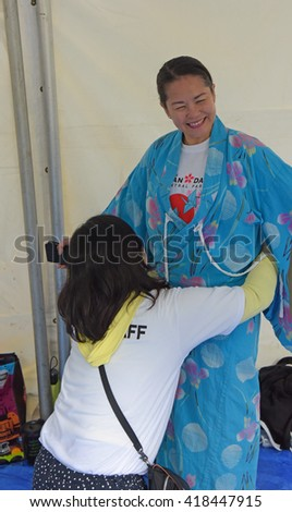 NEW YORK CITY - MAY 8 2016: the 10th annual Japan Day festival took place in Central Park starting with a NYRR sponsored Kids' Run. Trying on kimonos