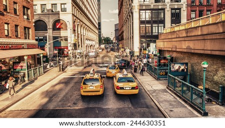 NEW YORK CITY - MAY 24: Yellow cabs speed up along city skyscrapers on May 24, 2013 in New York City. There are actually more than 13,000 yellow cabs in NYC - stock photo