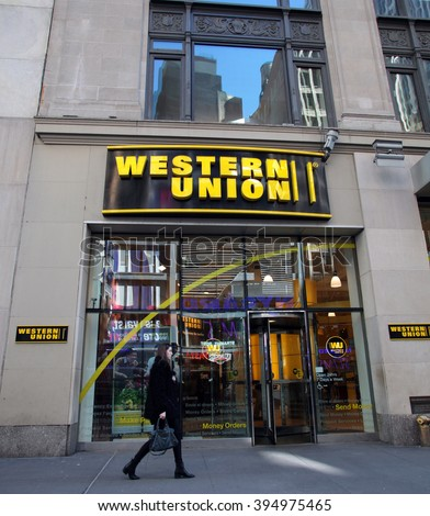 NEW YORK CITY - MONDAY, FEBRUARY 22, 2016: Pedestrians walk past a Western Union storefront. The Western Union Company is an American financial services and communications company