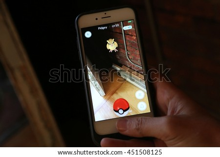 New York City, New York, USA; July 12, 2016; A woman battles Pidgey while playing the Nintendo game Pokemon Go on an iPhone.  - stock photo