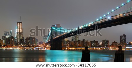 New York City night panorama with Brooklyn bridge and Manhattan skyline.