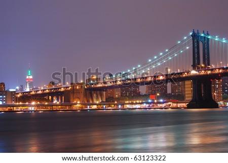 New York City night scene with Manhattan bridge and Empire State. Manhattan bridge connects new york and Brooklyn. - stock photo
