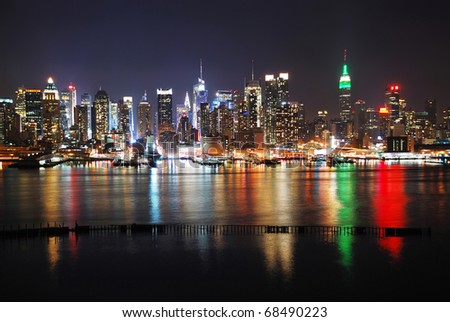 New York City night skyline panorama over Hudson river with boat and skyscraper and colorful reflections. - stock photo