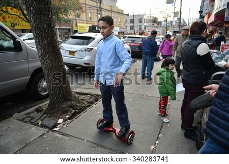NEW YORK CITY - NOV 12: A child rides a hoverboard on a street in a Brooklyn Chinatown on Nov 12, 2015 in New York City, USA. NYPD has since declared hoverboards or rideables are illegal in NYC. - stock photo