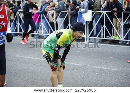 NEW YORK CITY - NOVEMBER 2 2014: the 43rd annual NYC Marathon saw more than 50,000 entrants race through all five boroughs. Exhausted male runner pauses with hands on knees yards from finish line - stock photo