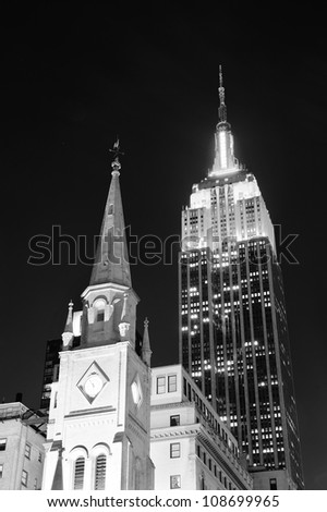 NEW YORK CITY, NY - DEC 30: Empire State Building and church on December 30, 2011 in New York City. It is a 102-story landmark and was world's tallest building for more than 40 years. - stock photo