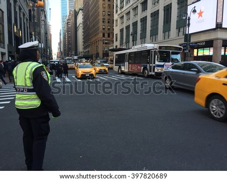 New York City, NY - March 29, 2016: A female NYPD police traffic cop observes passing rush hour commuter traffic on 7th Avenue in Manhattan outside Penn Station.