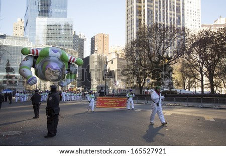 NEW YORK CITY, NY - NOVEMBER 28: Buzz Lightyear balloon flying by buildings in the Macy's 87th Annual Thanksgiving Day Parade on November 28, 2013 in New York City, New York.  - stock photo