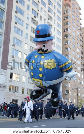 NEW YORK CITY, NY - NOVEMBER 24: NYPD Balloon floating down street during the Macy's 85th Annual Thanksgiving Day Parade on November 24, 2011 in New York City, New York. - stock photo