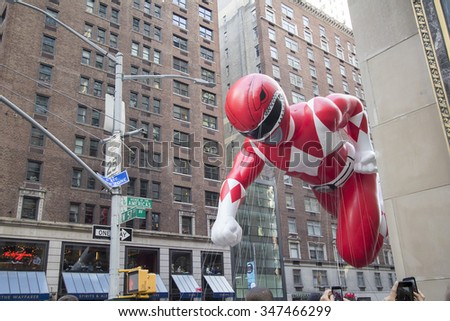NEW YORK CITY, NY - NOVEMBER 26: Red Power Ranger balloon flying between buildings in city street during the 89th Annual Macy's Thanksgiving Day Parade on November 26, 2015 in New York City - stock photo