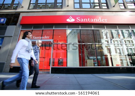 NEW YORK CITY - OCT 20 2013: Pedestrians walk past a branch of Santander Bank in Manhattan on Sunday, October 20, 2013.  - stock photo