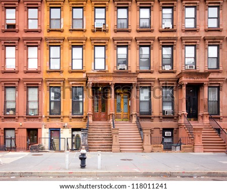 NEW YORK CITY - OCT 26: Row of 1880's historic NYC brownstones in Harlem on Oct 26, 2012. This historic neighborhood in Manhattan is a major African-American residential, cultural and business center - stock photo