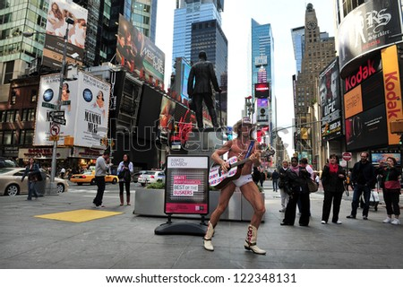 NEW YORK CITY - OCT 08 2010: The Naked Cowboy in Time Square in Manhattan New York City. Burck formally announced that he is running for President of the USA in the 2012 U.S. elections.  - stock photo
