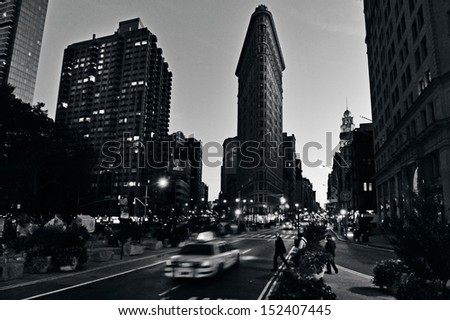 NEW YORK CITY - OCT 14: Traffic under Flat Iron building facade on Oct 14, 2009 in Manhattan New York at night.It's considered to be one of the first skyscrapers ever built completed in 1902. (B/W) - stock photo