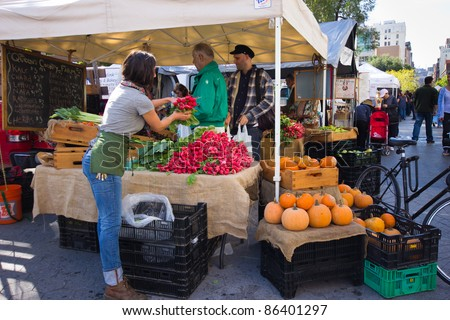NEW YORK CITY - OCT. 7:  Woman sells produce at Union Square Greenmarket in New York City on Oct. 7, 2011.  This world famous farmers' market began in 1976 and has grown to 140 farmers during peak season. - stock photo